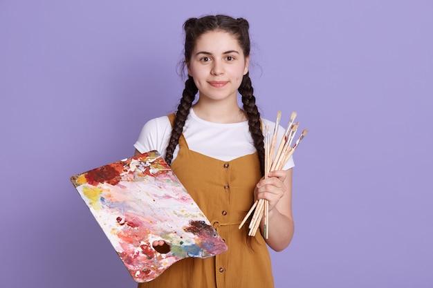 아름 다운 수채화 꽃 디자인을 만드는 재능있는 여자 캐주얼 복장을 입고 라일락 벽을 통해 격리 된 서. 무료 사진