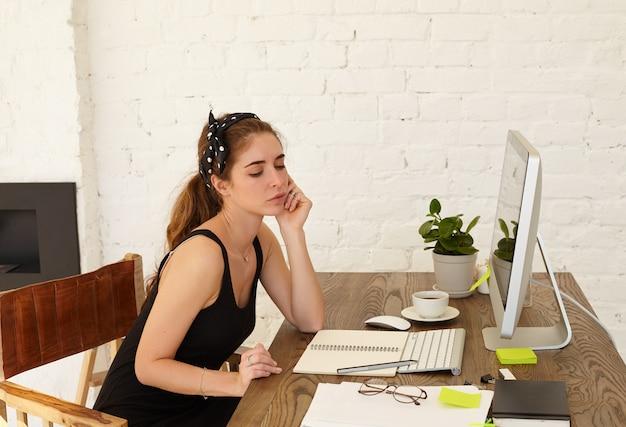 La talentuosa giovane designer femminile pensa al design del nuovo bar lavorando come freelance a casa. attraente giovane donna caucasica con emozione premurosa su un viso, guardando pensieroso sul posto di lavoro Foto Gratuite