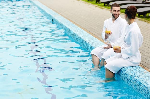 Talk by swimming pool Free Photo