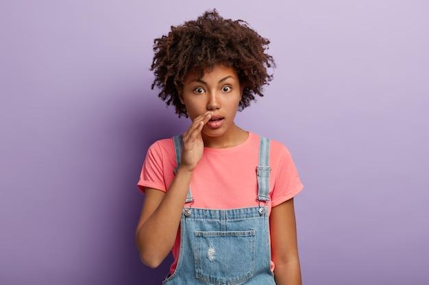 Болтливая впечатленная темнокожая самка держит руку у рта, рассказывает шокирующие сплетни, делится ужасными слухами Бесплатные Фотографии