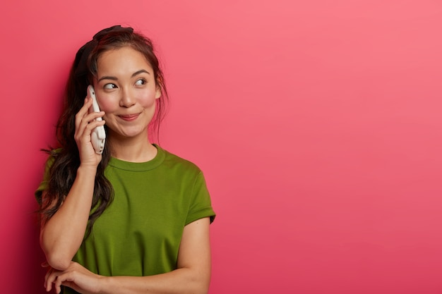 おしゃべりな10代の少女は、スマートフォンで何時間も話し、携帯電話を耳に近づけ、友達に電話をかけ、素敵な会話を楽しみ、思いやりのある表情を脇に置き、カジュアルな服装をしています。 無料写真