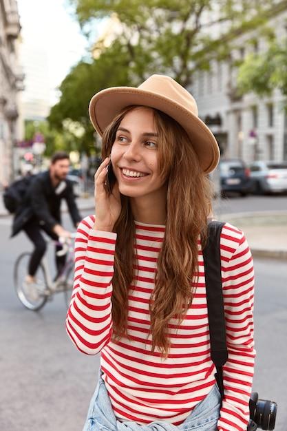 La giovane femmina loquace ha una conversazione telefonica con un amico Foto Gratuite