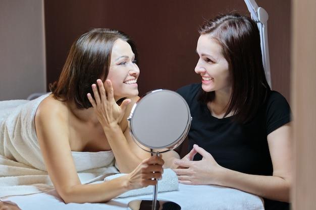 美容サロンの鏡で話していると笑顔の女性美容師と成熟した女性患者 Premium写真