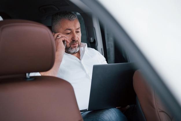 Говорить по телефону. работа на задней части автомобиля с использованием серебристого ноутбука. старший бизнесмен Бесплатные Фотографии