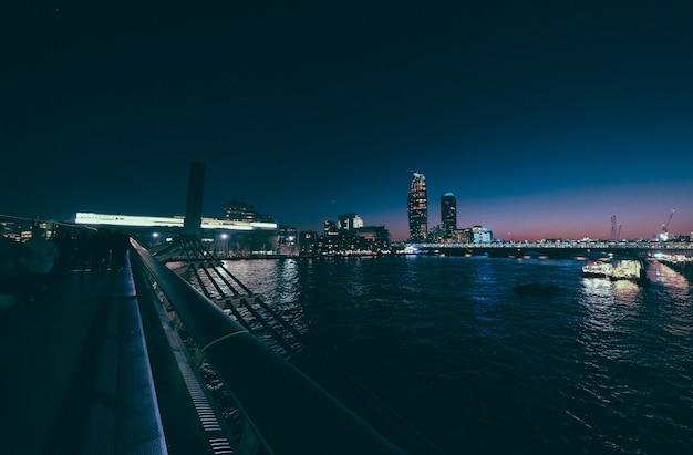 Высотное и городское здание на расстоянии выстрела от моста миллениум в ночное время Бесплатные Фотографии