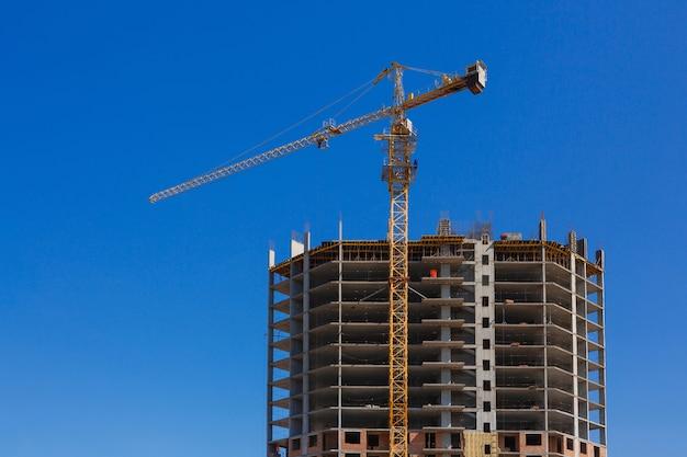 Высокое здание строится против неба. Premium Фотографии