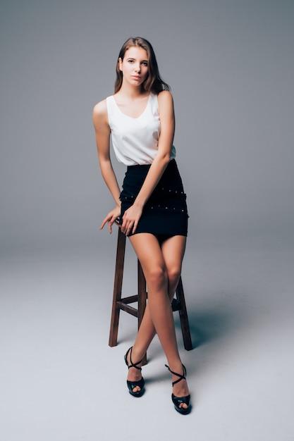 厳格な古典的な服で背の高いセクシーな細いブルネットの少女は、白い背景の前にスタジオの高い椅子に座っています。 無料写真