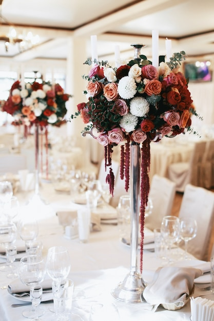 Tall Steel Vases With Red Bouquets Stand On Long Beige Table Photo