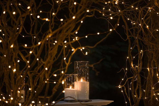 Tall Vases With White Candles Stand Under Shiny Branches Photo