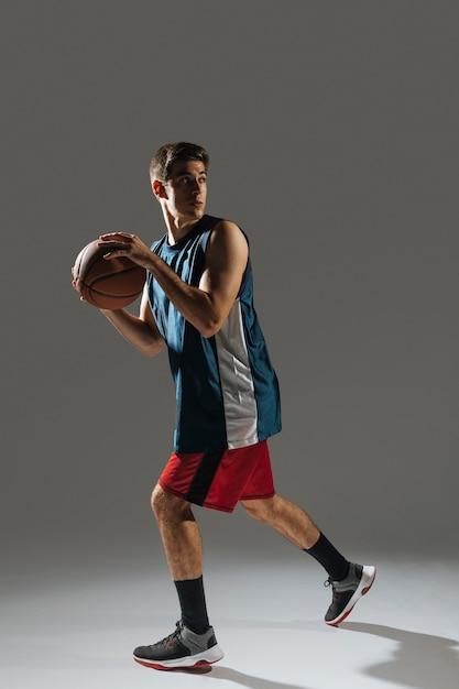 Высокий молодой человек тренируется для игры в баскетбол Бесплатные Фотографии