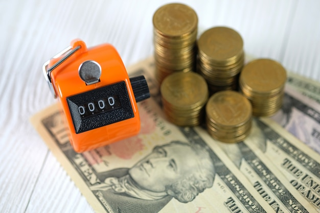 Tally counter or counting machine with 0000 number, coin and banknote on wood Premium Photo