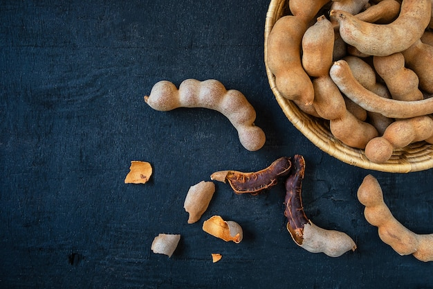 Tamarind in a wooden basket on the table Premium Photo