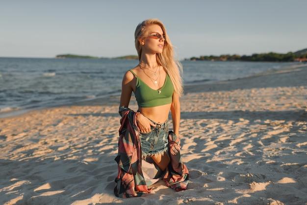 Загорелая стройная женщина с длинными светлыми волосами позирует на тропическом пляже. Бесплатные Фотографии
