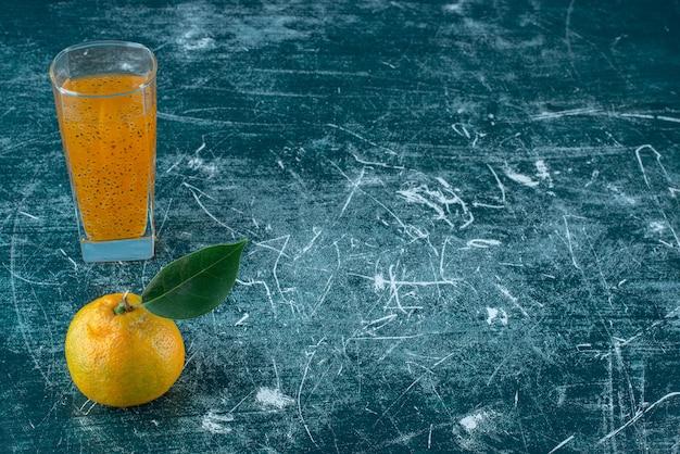 みかんと青い背景のジュースのガラス。高品質の写真 無料写真