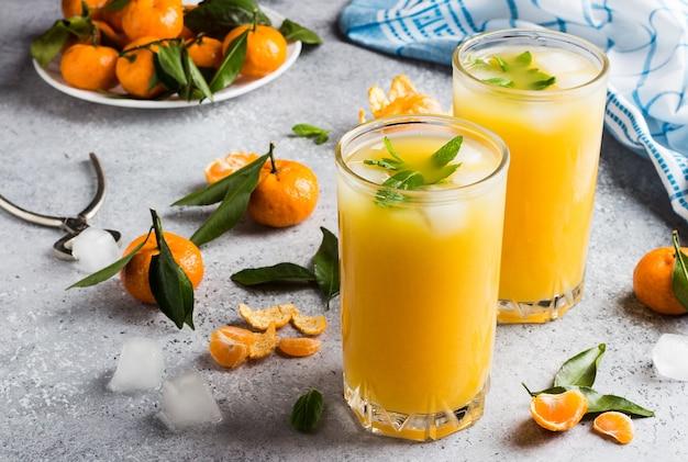 Tangerine juice in glasses on light Free Photo