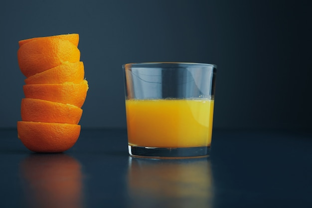 Tangerine peel coat near glass with fresh healthy citrus orange juice for breakfast, isolated on rustic blue table side view Free Photo