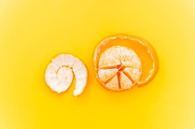 Tangerine on yellow background Free Photo