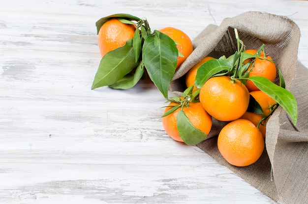 Tangerines clementine with leaves on a wooden table. Premium Photo