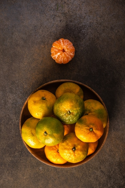 Tangerines or mandarines in bamboo bowl and ripe one on wooden background top view vertical orientation Premium Photo
