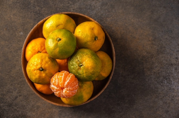 Tangerines or mandarines in bamboo bowl on wooden background top view Premium Photo