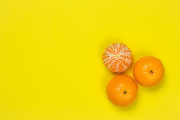 Мандарины на желтой бумажной стене. яркая рамка с мандаринами, копией пространства для текста. шаблон, выкройка. вид сверху цитрусовых. весело летнее настроение концепции. Premium Фотографии