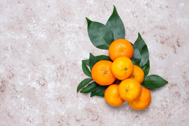 Tangerines (oranges, clementines, citrus fruits) with green leaves on concrete surface with copy space Free Photo