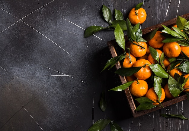 Tangerines with green leaves in wood box on dark Free Photo