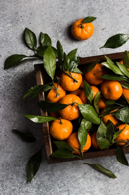 Tangerines with green leaves in wood box on light Free Photo