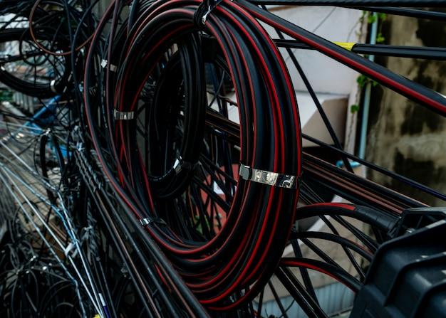 都市の電柱のもつれた電線。組織管理の概念が乱雑で乱雑。クローズアップのもつれた電線。 Premium写真