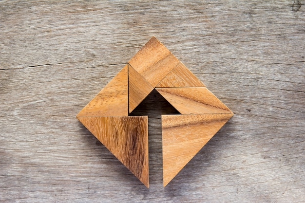 Tangram puzzle as arrow in square shape on wooden background Premium Photo