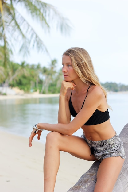 열 대 해변에서 야자수에 검게 맞는 슬림 백인 모델 무료 사진