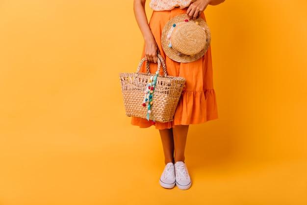 주황색 치마와 노란색에 서있는 흰색 신발에 검게 그을린 된 소녀. 스튜디오에서 포즈 유행 모자와 함께 화려한 여성 모델. 무료 사진