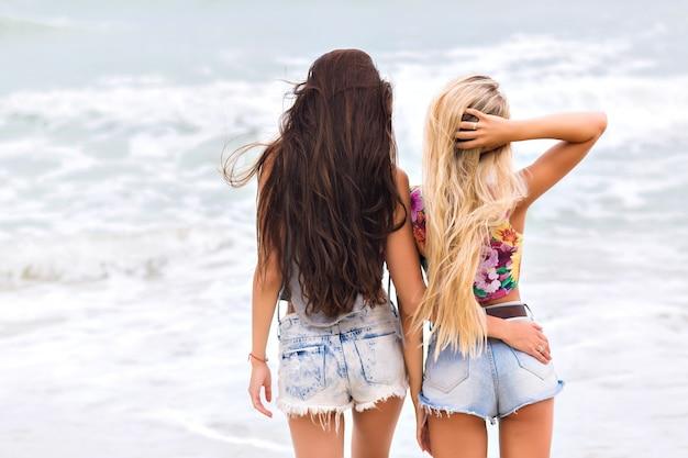海の近くに立って、素晴らしい自然の景色を楽しんでいる長い脚を持つ日焼けした女の子。海で朝を過ごすデニムショートパンツで裸足の女性の屋外の全身肖像画。 無料写真