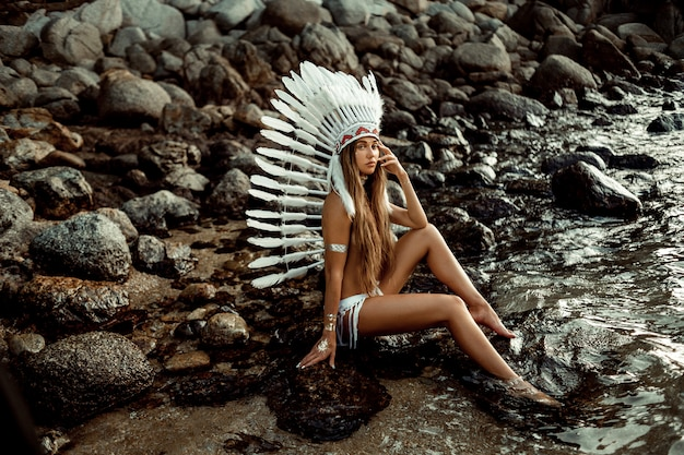Tanned young boho style women with white big feather hat and flash tattoo sitting rocky beach.   of style and themed holidays Premium Photo