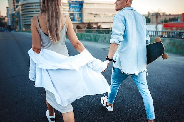 Giovane coppia caucasica abbronzata, storia d'amore moderna con effetto grana della pellicola e stile vintage. ora del tramonto. camminando per le strade della città, calda sera d'estate Foto Gratuite