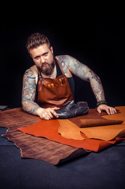 Кожевник работает с кожей, используя ремесленные инструменты в мастерской. / кожевник, производящий кожаные изделия в мастерской. Premium Фотографии