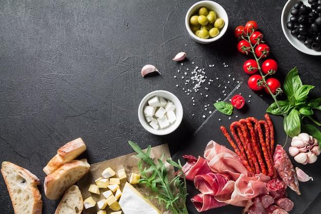 Концепция тапас. прошутто, колбаса чоризо, оливки, помидоры черри, руккола, базилик и сыр бри на черной грифельной доске. антипасти концепция. Premium Фотографии