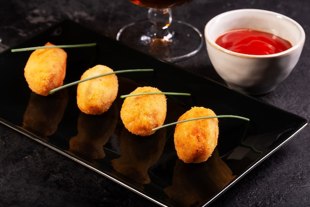 Крокеты тапас, традиционные испанские или французские закуски с красным соусом Premium Фотографии