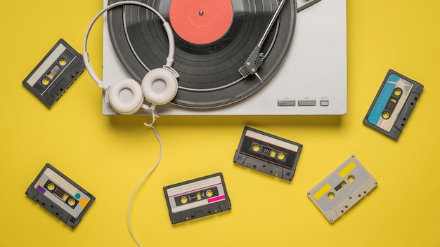 Tape cassettes, a vinyl record player, and headphones on yellow Premium Photo
