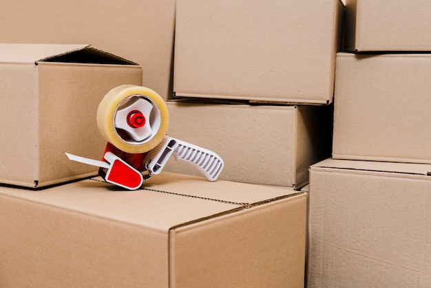 Tape dispenser on the closed cardboard boxes Free Photo