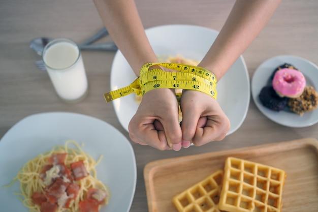 女性の腕の周りの巻尺。トランス脂肪、スパゲッティ、ドーナツ、ワッフル、お菓子を食べるのをやめます。健康のために体重を減らす。トップビューダイエットコンセプト Premium写真