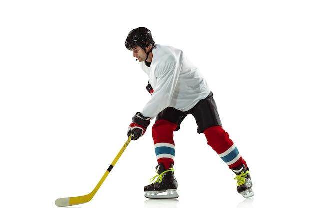 표적. 얼음 코트와 흰 벽에 막대기로 젊은 남자 하키 선수. 장비와 헬멧 연습을 착용하는 스포츠맨. 스포츠, 건강한 라이프 스타일, 운동, 운동, 행동의 개념. 무료 사진