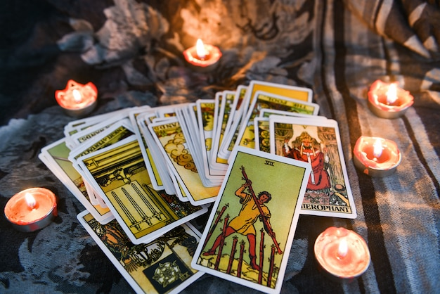 Tarot card with candlelight on the darkness background for astrology occult magic illustration - magic spiritual horoscopes and palm reading fortune teller concept Premium Photo