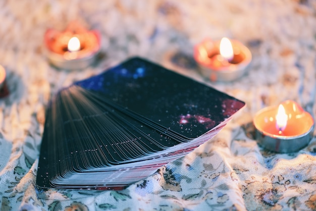 Tarot card with candlelight on the darkness background for astrology occult magic illustration / magic spiritual horoscopes and palm reading fortune teller Premium Photo