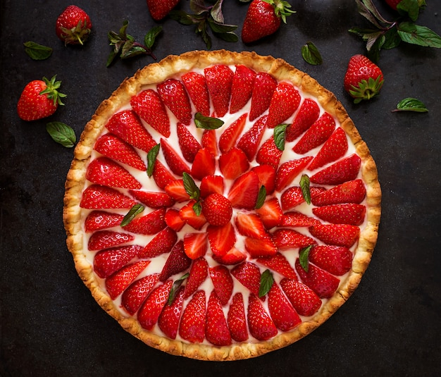 Tart with strawberries and whipped cream decorated with mint leaves. top view Free Photo