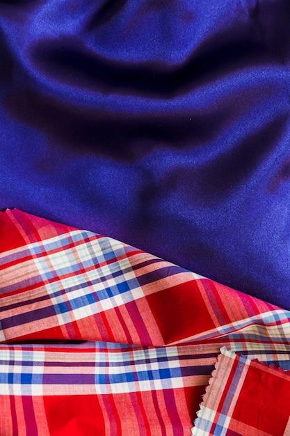 Tartan cotton material on plain blue textile Free Photo