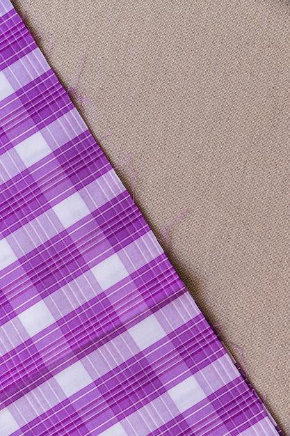 Tartan plaid fabric on plain textile Free Photo