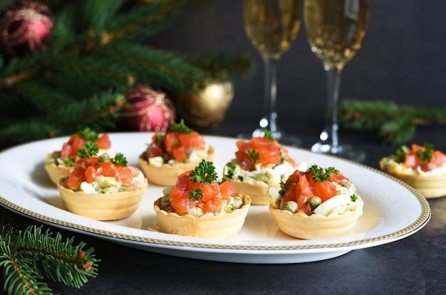 新年のテーブルにサラダとサーモンを詰めたタルト。シャンパングラスのあるお祭りテーブル Premium写真