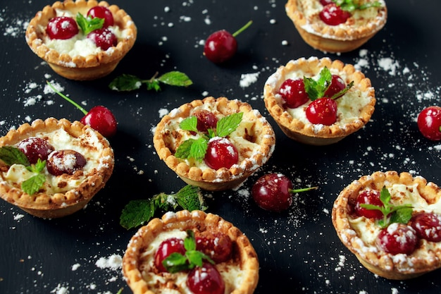 Tartlets with whipped cream and cherry. Premium Photo
