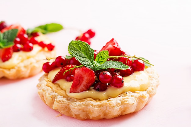 Tarts with strawberries, currant and whipped cream decorated with mint leaves Free Photo